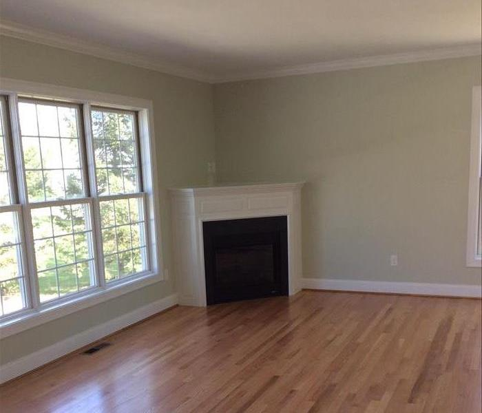 The image shows a Simsbury living room fully restored from fire damage with cleaned floors and painted walls.