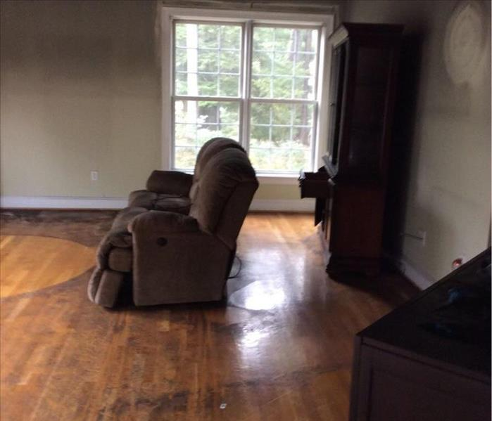 Image shows fire damage to walls, upholstered furniture, and floor in Simsbury home