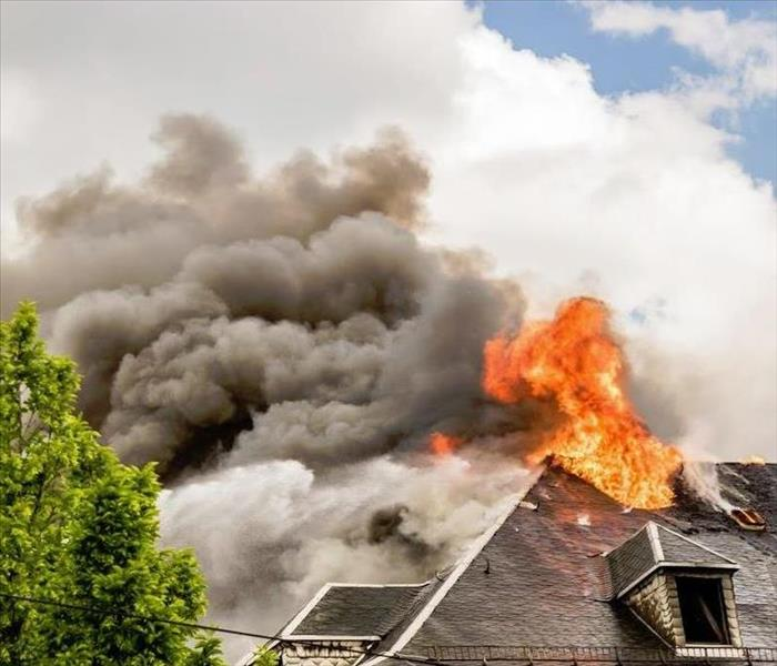 fire burning through the roof of a house