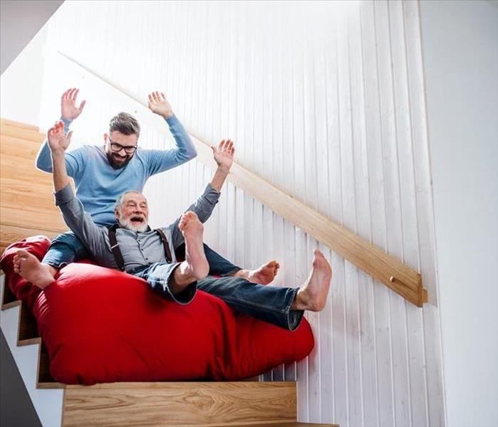 Two men sitting on a red cushion going down a flight of stairs.